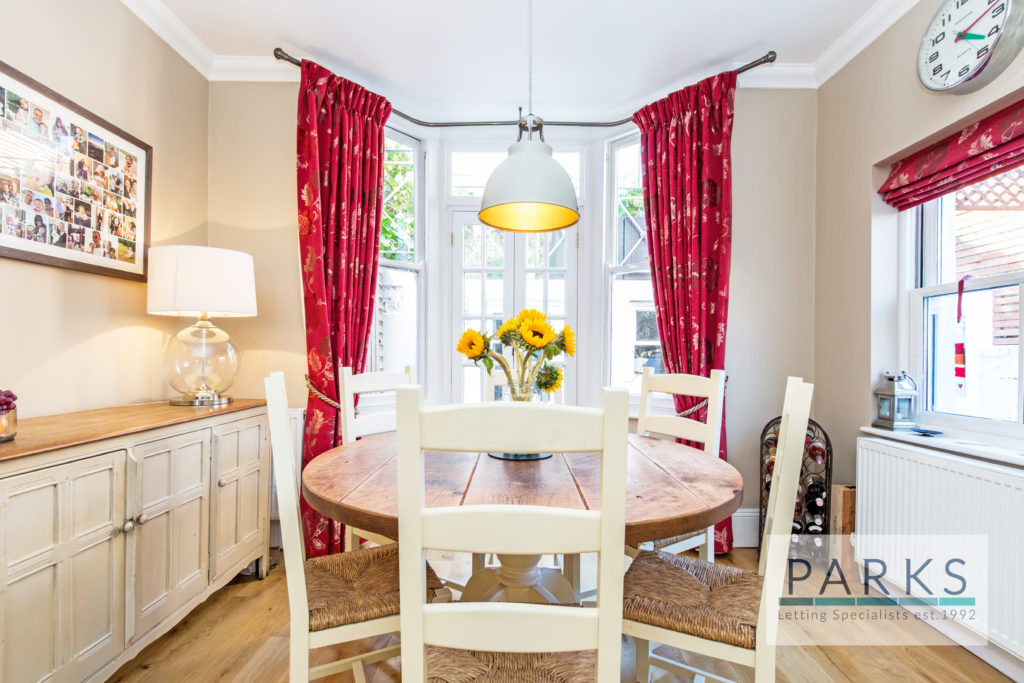 furnished dinning room with side board and large bay window